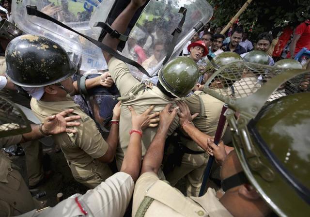 Varios miembros del Partido Comunista se enfrentan a la policía durante una manifestación en apoyo a los granjeros en Calcuta, India, hoy 27 de agosto de 2015. La ley de tierras promovida por el Gobierno ha provocado protestas y malestar en la comunidad agrícola en los últimos meses. EFE/Piyal Adhikary