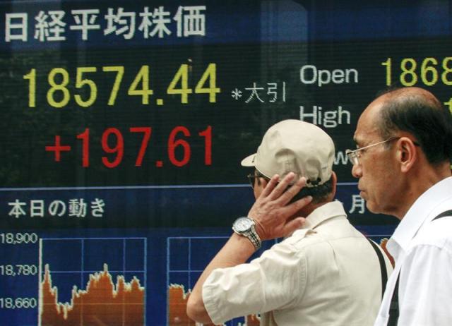 Dos hombres caminan junto a una pantalla que muestra información bursátil en el centro de Tokio (Japón) hoy, 27 de agosto de 2015. La Bolsa de Tokio volvió a subir hoy más de un 1 por ciento en medio de un renovado optimismo generado por el repunte bursátil mundial en el que destacaron las ganancias récord en Wall Street. El índice Nikkei de la Bolsa de Tokio cerró con una subida de 197,61 puntos, un 1,08 por ciento, y se situó en las 18.574,44 unidades. EFE/Kimimasa Mayama