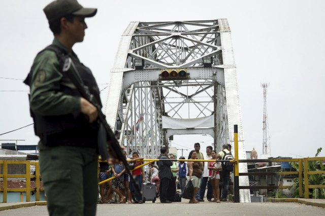 People stand next to a closed gate while a Venezuelan soldier stands guard at La Union international bridge, on the border with Colombia at Boca de Grita in Tachira state, Venezuela