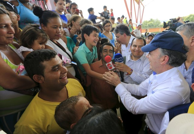 Colombia's President Juan Manuel Santos greets people deported from Venezuela during a visit at a temporary shelter in Villa del Rosario