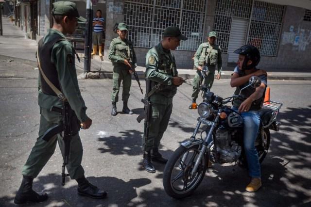 CAR12. SAN ANTONIO (VENEZUELA), 30/08/2015.- Integrante del ejército venezolano inspeccionan a un motociclista en las inmediaciones de la Aduana Principal fronteriza entre Colombia y Venezuela hoy, domingo 30 de agosto de 2015, en la ciudad de San Antonio (Venezuela). El Gobierno de Venezuela reiteró hoy que el cierre de parte de la frontera solo ha generado beneficios a su país después de que las autoridades hicieran un recorrido para confirmar que la medida se está cumpliendo en 140 kilómetros de los límites con Colombia. El presidente de Venezuela Nicolás Maduro decidió cerrar parte de la frontera con Colombia la medianoche del 19 de agosto después de que tres militares y un civil venezolanos resultasen heridos en un ataque de supuestos contrabandistas en la zona limítrofe a lo que sumó, dos días después, el decreto de estado de excepción en la zona. EFE/MIGUEL GUTIÉRREZ