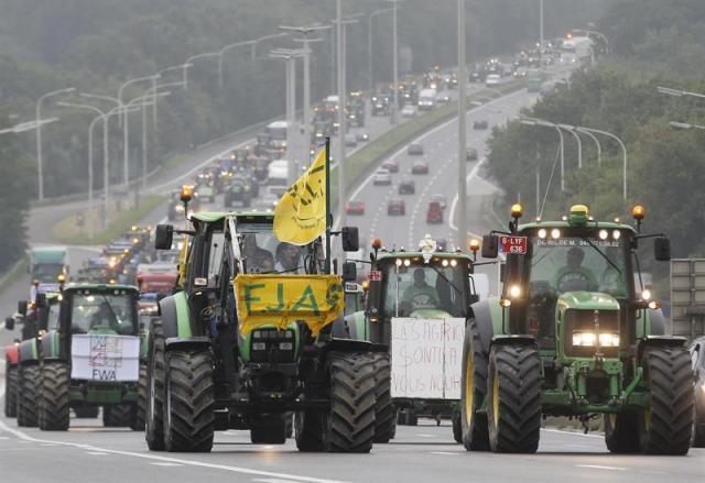 """Tractores ruedan por la autovía E411 con dirección a las sedes de las instituciones de la UE en Bruselas (Bélgica), hoy, 7 de septiembre de 2015. Miles de tractores y agricultores de toda Europa llegaron a Bruselas desde distintos puntos de Bélgica para protestar por la bajada del precio de la leche, el mismo día que los ministros europeos de Agricultura celebran un Consejo extraordinario para buscar soluciones a la crisis agroalimentaria. Las protestas han causado fuertes perturbaciones del tráfico en todo el país desde primera hora de la mañana, con 200 kilómetros de retenciones, informa el diario """"Le Soir"""". EFE/OLIVIER HOSLET"""