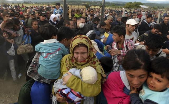 """Refugiados logran romper el cordón policial y cruzar a Gevgelija, ciudad macedonia situada en la frontera con Grecia, hoy, 7 de septiembre de 2015. Millares de refugiados, la mayoría sirios, emprenden una ardua travesía a través de la conocida como """"ruta de los Balcanes"""", que pasa por Grecia, Macedonia y Serbia hasta llegar a Hungría, en un anhelo por alcanzar Europa occidental. EFE/Nake Batev"""