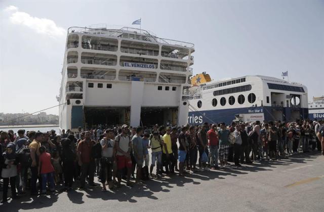 """Refugiados, en su mayoría sirios, suben a un autobús tras desembarcar del ferry """"Eleftherios Venizelos"""" en el puerto del Pireo en Grecia hoy, 8 de septiembre de 2015. Más de 2.000 refugiados llegaron esta mañana al puerto del Pireo, en Atenas, procedentes de la isla de Lesbos, la más afectada del mar Egeo por la ola de migración, con alrededor de 20.000 personas todavía atrapadas allí. Los 2.187 refugiados, en su mayoría sirios, llegaron a bordo del transbordador Eleftherios Venizelos que desde hace varias semanas hace a diario la ruta entre las islas del Egeo cercanas a la costa turca y la plataforma continental. EFE/Yannis Kolesidis"""
