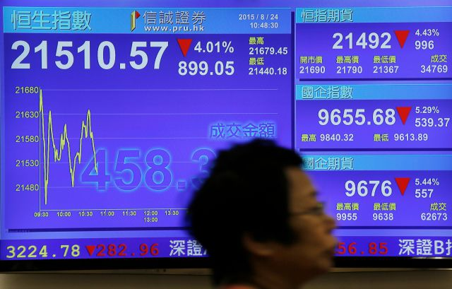 A woman walks past an electronic board showing the Hong Kong share index at a Hong Kong local security company in Hong Kong, Monday, Aug. 24, 2015. Stocks fell in early trading Monday in Asia as investors shaken by the sell-off last week on Wall Street unloaded shares in many sectors. (AP Photo/Vincent Yu)
