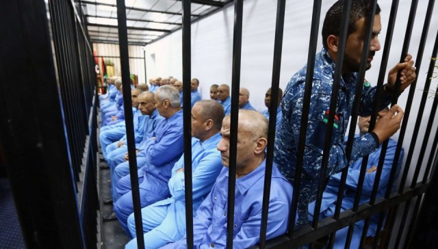 Members of the former Libyan regime sit dressed in prison blues behind bars during a hearing for their trial in Tripoli. Thirty-seven former Gadhafi regime officials are charged with murder, kidnapping, complicity in incitement to rape, plunder, sabotage, embezzlement of public funds and acts harmful to national unity.  Mahmud Turkia, AFP/Getty Images