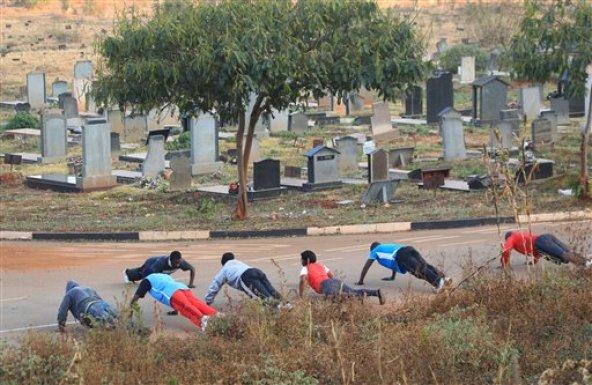 Varias personas hacen gimnasia el 25 de julio del 2015 en el cementerio de Warren Hills en Harare, Zimbabue. Muchos entusiastas de la preparación física aprovechan las zonas mejor cuidadas del camposanto para hacer ejercicios. (AP Foto/Tsvangirayi Mukwazhi)