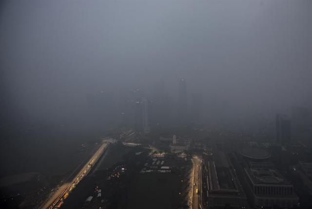 El humo y la niebla envuelven el distrito financiero de Singapur en el que se aprecia parte del circuito urbano de Marina Bay de Fórmula Uno hoy, 14 de septiembre de 2015. La Agencia de Medioambiente de Singapur ha anunciado que la contaminación es de 152 PSI, nada saludable para el ser humano según la agencia, debido al humo que proviene de la quema de cultivos en Indonesia cuyos incendios provocan que el humo contamine Singapur. EFE/Wallace Woon