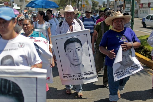 A relative (C) of Mexican missing student Jhosivani Guerrero de la Cruz holds his portrait during a march in Acapulco, Guerrero State, Mexico, on March 4, 2015. Jhosivani Guerrero is the second of the 43 missing students of Ayotzinapa whose remains are identified, the Mexican government informed on September 16, 2015.  AFP PHOTO / Pedro PARDO