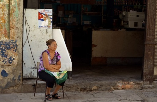 A woman sits outside her shop by a portratit of Pope Francis marking his upcoming visit to Cuba in a street of Havana on September 18, 2015.  AFP PHOTO / FILIPPO MONTEFORTE