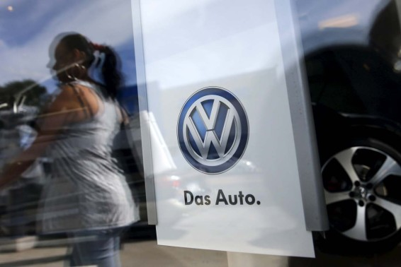 A woman is seen reflected on the window of a Volkswagen dealership in the Queens borough of New York, September 21, 2015. Volkswagen shares plunged more than 20 percent on Monday, their biggest ever one-day fall, after news that the German carmaker had rigged U.S. emissions tests, and Germany said it would investigate whether data had been falsified in Europe too. REUTERS/Shannon Stapleton