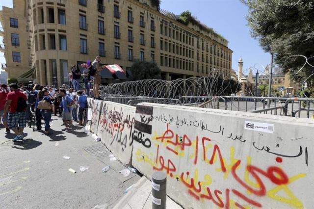 Manifestantes protestan junto a unas barreras que protegen el Parlamento en Beirut (Líbano) hoy, 22 de septiembre de 2015. EFE/Nabil Mounzer