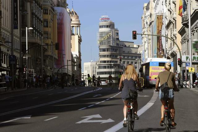 """Dos mujeres recorren en bicicleta la Gran Vía de Madrid cerrada al tráfico con motivo del Día Sin Coches que, además de Madrid, celebran Valladolid, San Sebastián, y Valencia, entre 330 ciudades, con acciones que van desde limitar el tráfico privado en algunas áreas y franjas horarias a ofrecer transporte público gratuito o reducir la velocidad para """"pacificar"""" el ambiente urbano. EFE/Mariscal"""