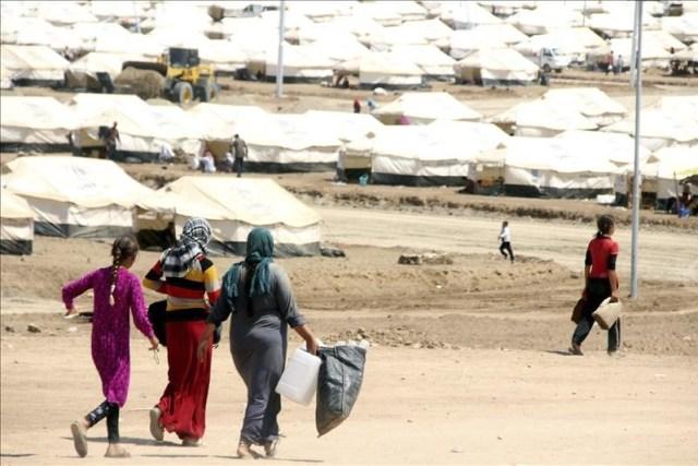 Varias mujeres se dirigen a recoger agua en un campo de refugiados cerca del puesto fronterizo