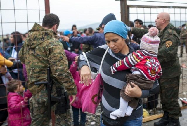Policías macedonios controlar a una multitud de los migrantes y refugiados, mientras se preparan para entrar en un campamento después de cruzar la frontera con Grecia en Macedonia, cerca de Gevgelija el 8 de octubre de 2015. Macedonia es un país de tránsito clave en la ruta de migración de los Balcanes en la UE, con miles de solicitantes de asilo y migrantes - muchos de ellos procedentes de Siria, Afganistán, Irak y Somalia - que entran en el país todos los días. AFP PHOTO / ROBERT Atanasovski