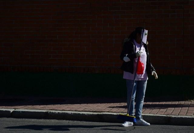 """A las prostitutas con una máscara de disfraces sostiene una escoba durante una actuación de protesta convocada por AFEMTRAS, la red de trabajadoras sexuales de la mujer, """"para limpiar la calle de los verdaderos problemas: la falta de convivencia, los estereotipos, los insultos y estigma social"""", en un intento para generar mejores relaciones de vecindad en el distrito industrial Marconi de Madrid el 14 de octubre de 2015. AFP PHOTO / PIERRE-PHILIPPE MARCOU"""
