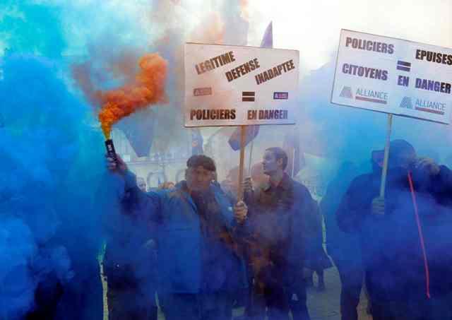 """La policía francesa están detrás de las banderas sindicales que protestan cerca del Ministerio de Justicia en París, Francia, 14 de octubre de 2015. Miles de policías protestaron en las afueras del Ministerio de Justicia de Francia por primera vez en décadas el miércoles para denunciar la falta de recursos y lo que dicen es insuficiente apoyo del poder judicial en su trabajo diario cumplimiento de la ley. El lema lee """"inadecuada autodefensa = policial en peligro"""". REUTERS / Jacky Naegelen"""