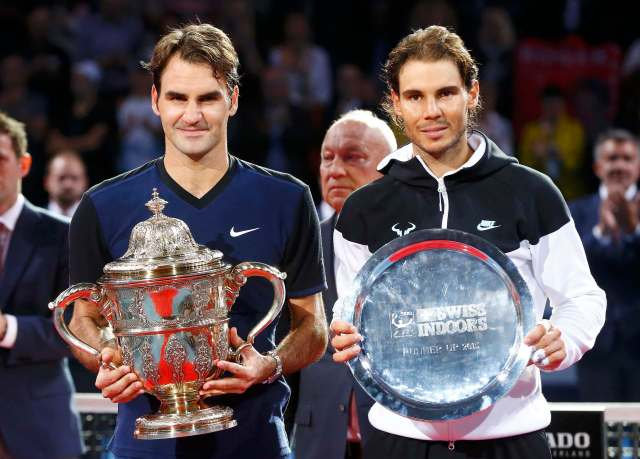 Switzerland's Roger Federer (L) holds the trophy after winning his match against Rafael Nadal of Spain at the Swiss Indoors ATP men's tennis tournament in Basel, Switzerland November 1, 2015.   REUTERS/Arnd Wiegmann