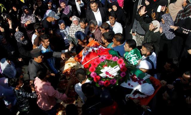Palestinos ondean banderas durante el entierro de Muhammed Shamasne en Qatna (Palestina) hoy, 2 de noviembre de 2015. El gobierno israelí entregó ayer los cuerpos sin vida de dos palestinos que fueron abatidos tras atacar a israelíes tras exigir a las autoridades palestinas que se mantendría la calma durante sus entierros. Además, Israel ha exigido que los rituales se celebren por la noche y sólo a los familiares más cercanos para evitar que se glorifique a los fallecidos. EFE/Alaa Badarneh