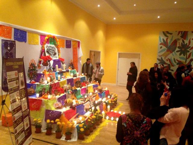 Varias personas observan el tradicional altar que la embajada de México en Pekín ha instalado para honrar a los difuntos, una costumbre que se repite cada año en la capital china pero esta vez va acompañada de cursos para que los niños se introduzcan en esa peculiar manifestación de la cultura mexicana. EFE/Antonio Broto.