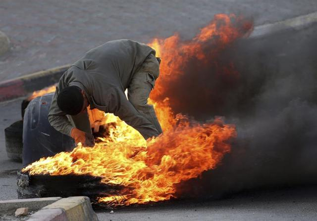 Un manifestante palestino quema unos neumáticos usados para levantar una barricada durante los enfrentamientos con las fuerzas de seguridad israelíes en Beit Ommar, en la localidad cisjordana de Hebrón (Palestina) hoy, 3 de noviembre de 2015. Por otro lado, las fuerzas israelíes clausuraron esta madrugada la emisora de radio palestina Al-Hurriya acusada de incitar a la violencia. EFE/Abed Al Hashlamoun