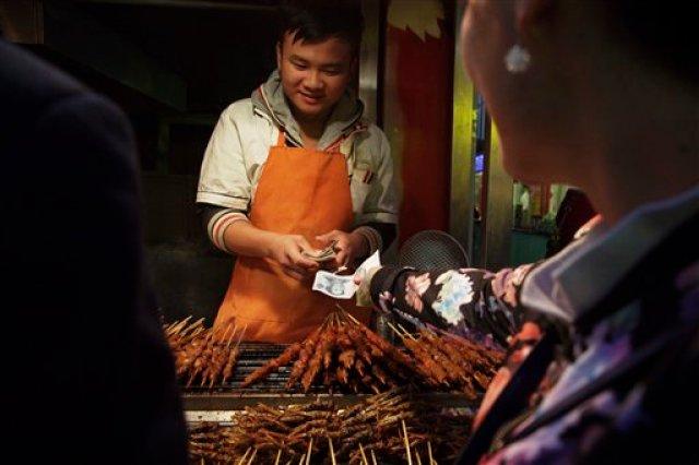 En esta foto tomada el jueves 29 de octubre de 2015, un vendedor ambulante cobra dinero en Beijing, China. China anunció el martes 3 de noviembre de 2015 que permitirá a su estrictamente controlado yuan cotizar libremente para 2020, lo que potencialmente aliviaría las tensiones comerciales con Estados Unidos y otras naciones.(Foto AP/Ng Han Guan)