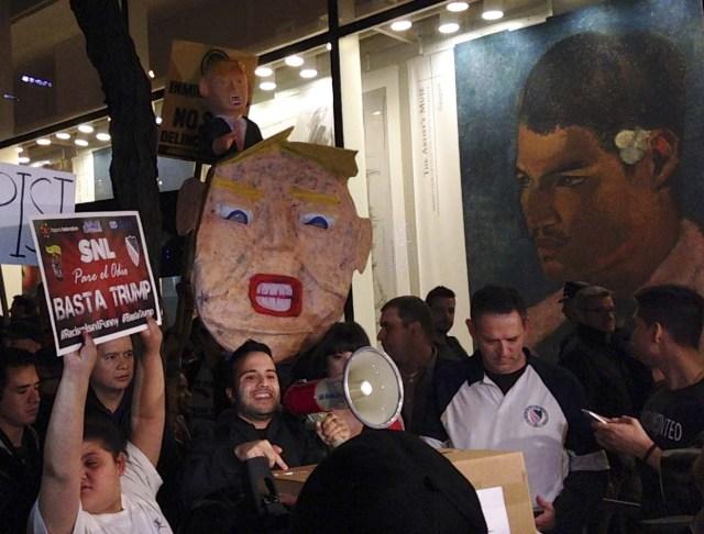 """Manifestantes marchan en protesta contra los puntos de vista de Donald Trump en materia de inmigración, horas antes de su participación en el programa """"Saturday Night Live"""", el sábado 7 de noviembre de 2015, en la ciudad de Nueva York. (Foto AP/Katie Park)"""