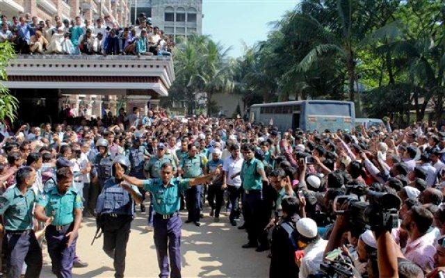 La gente de Bangladesh se reúne afuera de un tribunal mientras la policía escolta al joven acusado de matar al niño bangladesí Samiul Islam Rajon, antes del veredicto en Sylhet, Bangladesh, el domingo 8 de noviembre de 2015. Rajon, de 13 años, murió en julio después de ser golpeado brutalmente. El principal sospechoso de la muerte de Rajon, Kamrul Islam, y otros tres culpables de torturar al chico, fueron sentenciados a muerte. (Foto AP/ A.H.Arif)