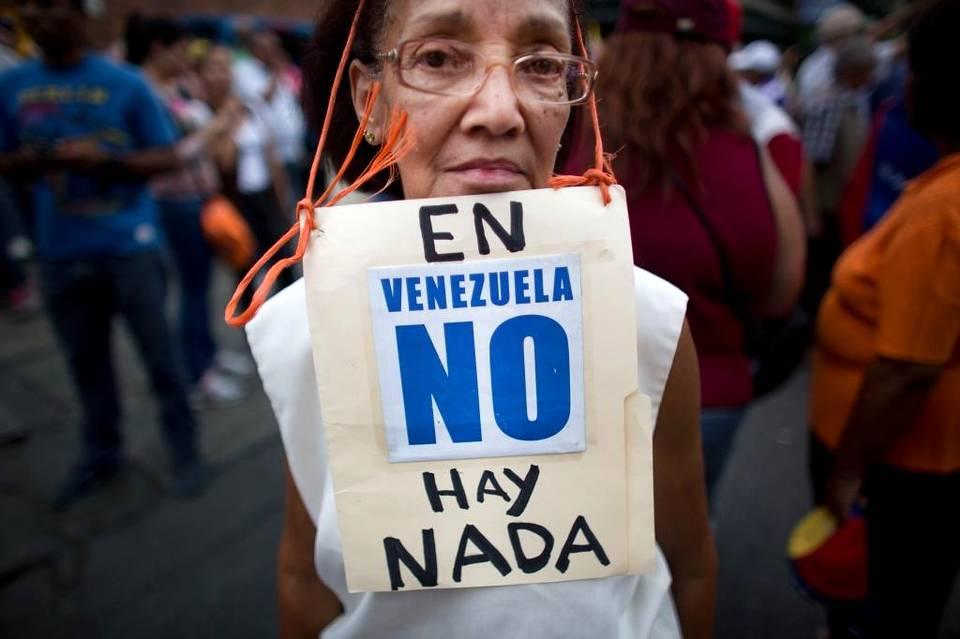Beatriz Silva, de 74 años, lleva un letrero que condena la escasez en Venezuela, en una protesta en la capital, en agosto. Ariana Cubillos AP