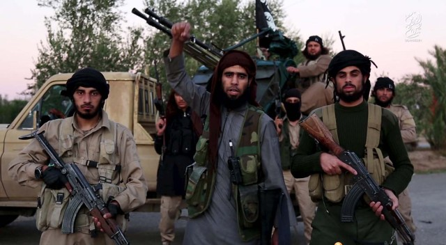 A man (C) identified in the subtitiles as Al Karar the Iraqi gestures as he speaks at an undisclosed location in this image taken from undated video footage released by Islamic State. Islamic State warned in the new video on November 16, 2015 that countries taking part in air strikes against Syria would suffer the same fate as France, and threatened to attack in Washington. The video, which appeared on a site used by Islamic State to post its messages, begins with news footage of the aftermath of Friday's Paris shootings in which at least 129 people were killed. REUTERS/Social Media Website via Reuters TVATTENTION EDITORS - THIS PICTURE WAS PROVIDED BY A THIRD PARTY. REUTERS IS UNABLE TO INDEPENDENTLY VERIFY THE AUTHENTICITY, CONTENT, LOCATION OR DATE OF THIS IMAGE. THIS PICTURE IS DISTRIBUTED EXACTLY AS RECEIVED BY REUTERS, AS A SERVICE TO CLIENTS. FOR EDITORIAL USE ONLY. NOT FOR SALE FOR MARKETING OR ADVERTISING CAMPAIGNS. NO RESALES. NO ARCHIVE.
