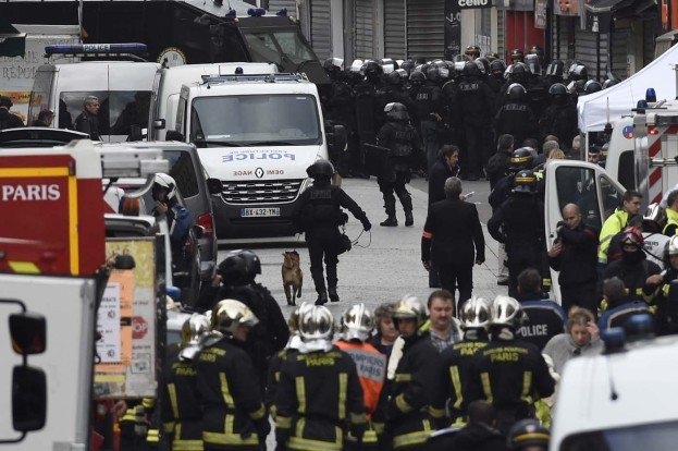 Firefighters and policemen are gathered in the northern Paris suburb of Saint-Denis city center, on November 18, 2015, as French Police special forces raid an appartment, hunting those behind the attacks that claimed 129 lives in the French capital five days ago. At least one person was killed in an apartment targeted in the operation aimed at the suspected mastermind of the attacks, Belgian Abdelhamid Abaaoud, and police had been wounded in the shootout.     AFP PHOTO / LIONEL BONAVENTURE