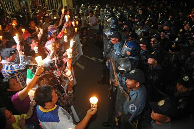 Policía manifestantes negros de vivir la Iglesia como pueblo indígena de Mindanao en el sur de encender velas Filipinas realizar una protesta en el interior de una iglesia en Manila el 18 de noviembre de 2015, contra la cumbre de Cooperación Económica Asia-Pacífico (APEC). AFP PHOTO /