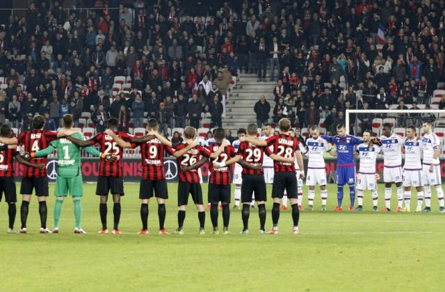 Jugadores del Niza, izquierda, y Lyon guardan un minuto de silencio previo a un partido de la liga francesa en Niza el viernes 20 de noviembre de 2015. (AP Foto/Lionel Cironneau)
