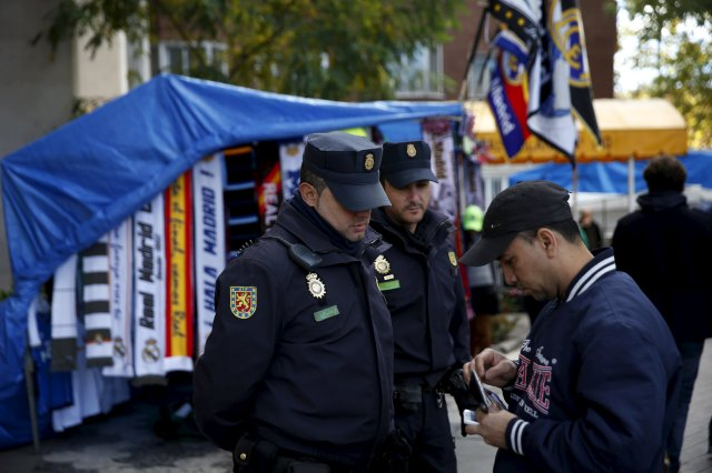 Spanish National Police officers check a man's identification as they stand guard outside the Santiago Bernabeu stadium before the 'Clasico' soccer match between Real Madrid and Barcelona in Madrid, Spain, November 21, 2015. REUTERS/Susana Vera