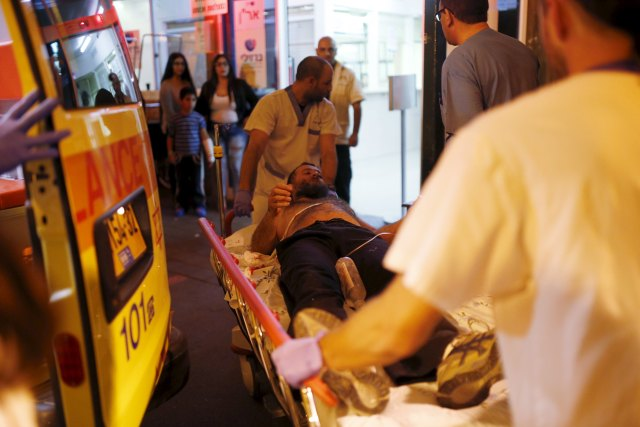 Israeli medics evacuate a man wounded in what Israeli police suspect might be a Palestinian stabbing attack, to Barzilai hospital in the southern city of Ashkelon, Israel November 21, 2015. REUTERS/Amir Cohen