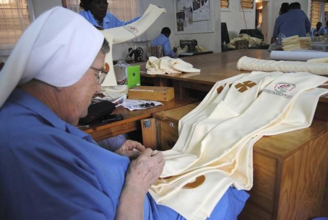 """GRA015. NAIROBI, 24/11/2015.- La hermana Ida Lagonegro, de 73 años, ultima una de las 2.000 estolas que han preparado con la inscripción """"Pope Francis 2015"""" y con una cruz bordada con tela africana que llevarán todos los sacerdotes que participen en la visita papal al continente africano. EFE/Jèssica Martorell"""