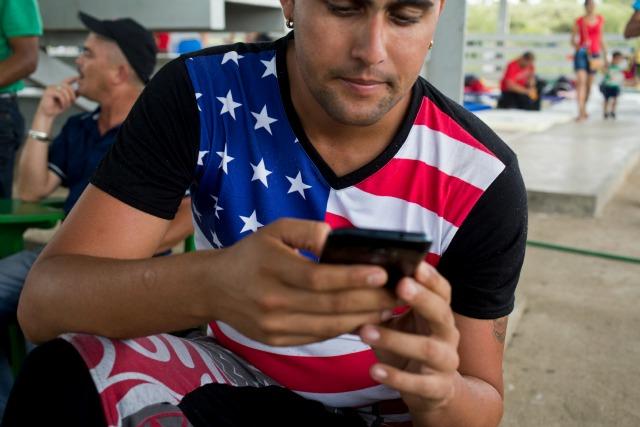 Esta fotografía del viernes 20 de noviembre de 2015 muestra a un inmigrante cubano con una camiseta con un diseño de la bandera de Estados Unidos mientras usa su celular en un refugio en La Cruz, Costa Rica, en la frontera con Nicaragua. Casi todos los cubanos entrevistados en refugios a lo largo de la frontera de Costa Rica con Nicaragua señalaron que los teléfonos inteligentes baratos, ciertos planes de datos y Facebook son el secreto de su éxito para llegar a la frontera con Estados Unidos. (Foto AP/Esteban Félix)