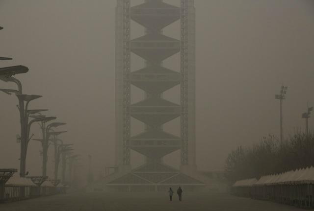 Los visitantes caminan hacia Linglong Torre durante un día extremadamente contaminado como peligrosos, asfixia contaminación sigue manta Beijing, China 01 de diciembre de 2015. REUTERS / Kim Kyung-Hoon