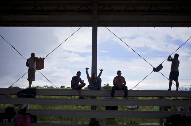 """En esta foto del sábado 21 de noviembre de 2015, migrantes cubanos descansan en un refugio en La Cruz, Costa Rica, cerca de la frontera con Nicaragua. Los gobiernos centroamericanos han convocado a una reunión de emergencia sobre la reciente crisis migratoria cubana el martes en El Salvador. Nicaragua, un aliado socialista cercano a Cuba, no ha respondido públicamente a una propuesta de Costa Rica de crear un """"corredor humanitario"""" para que los cubanos se desplacen sin obstáculos hacia Estados Unidos. (Foto AP/Esteban Félix)"""