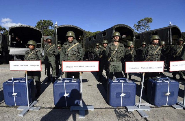 Members of the Venezuelan army stand next to electoral machines in Caracas on December 1, 2015. The Venezuelan opposition on Monday urged the armed forces to ensure that the results of the legislative elections of next Sunday are respected. AFP PHOTO/JUAN BARRETO / AFP / JUAN BARRETO