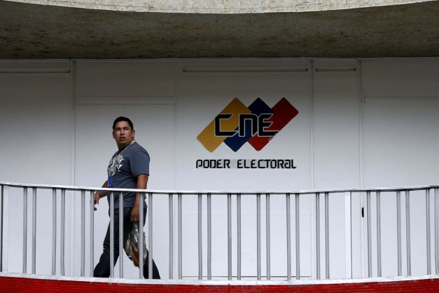 A man walks past a logo of the National Electoral Council (CNE) at its headquarters in Caracas December 2, 2015. Venezuela will hold parliamentary elections on December 6. REUTERS/Carlos Garcia Rawlins