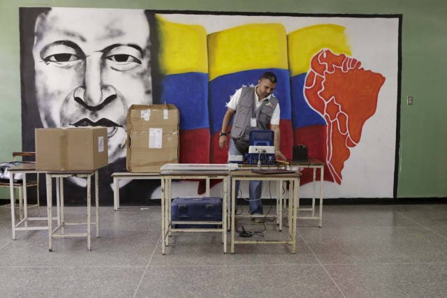 A worker of the National Electoral Council (CNE) configures a voting machine in front of a mural depicting Venezuela's late President Hugo Chavez at a school in Caracas, December 4, 2015. Venezuela will hold parliamentary elections on December 6. REUTERS/Marco Bello FOR EDITORIAL USE ONLY. NO RESALES. NO ARCHIVE.