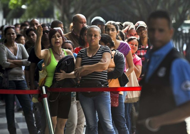 """People await in a popular market to buy food in Caracas on December 4, 2015. For the first time in 16 years of """"Bolivarian revolution"""" under late president Hugo Chavez and his successor Nicolas Maduro, polls show their rivals could now win a majority in the National Assembly. AFP PHOTO / LUIS ROBAYO / AFP / LUIS ROBAYO"""