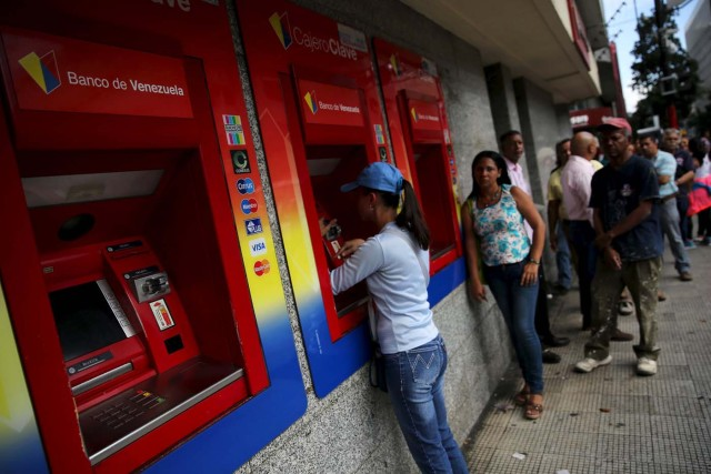 Venezuelans line up to withdraw cash from an automated teller machine (ATM) outside a Venezuela branch in Caracas December 4, 2015. Polarized Venezuela heads to the polls this weekend with a punishing recession forecast to rock the ruling Socialists and propel an optimistic opposition to its first legislative majority in 16 years. REUTERS/Nacho Doce