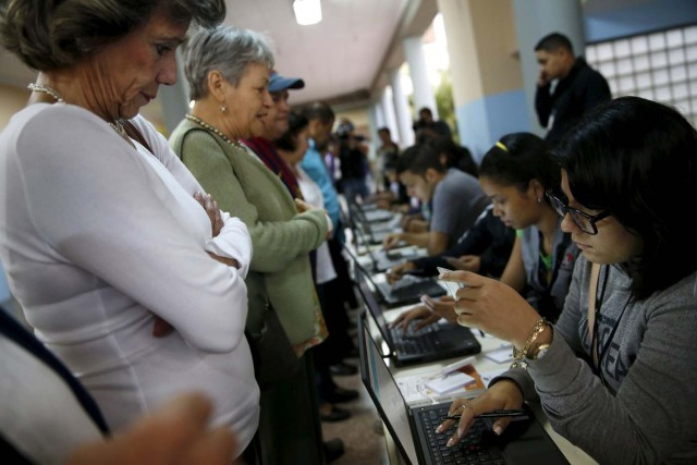 People register to cast their vote at a polling station during a legislative election, in Caracas December 6, 2015. REUTERS/Carlos Garcia Rawlins