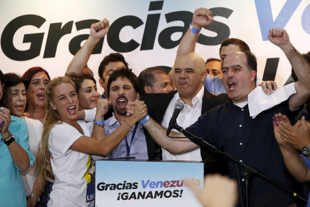 Lilian Tintori (centre L), wife of jailed Venezuelan opposition leader Leopoldo Lopez, celebrates next to candidates of the Venezuelan coalition of opposition parties (MUD) during a news conference on the election in Caracas early December 7, 2015. Venezuela's opposition won control of the legislature from the ruling Socialists for the first time in 16 years on Sunday, giving them a long-sought platform to challenge President Nicolas Maduro. REUTERS/Carlos Garcia Rawlins