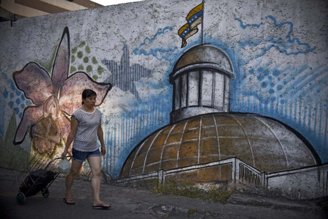 A woman walks past a mural depicting the National Assembly building in Caracas, on December 7, 2015. Venezuela's jubilant opposition vowed Monday to drag the oil-rich country out of its economic crisis and free political prisoners after winning control of congress from socialist President Nicolas Maduro. AFP  PHOTO/Luis Robayo / AFP / LUIS ROBAYO
