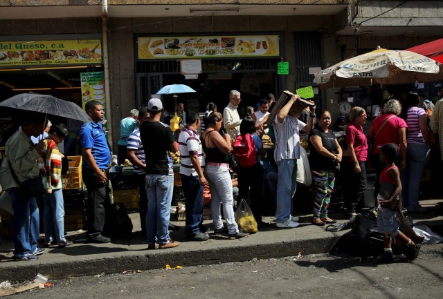 Alexandre (R), 7, sells plastic bags to citizens lining up to buy chicken at a store in Caracas, Venezuela December 8, 2015.  REUTERS/Nacho Doce