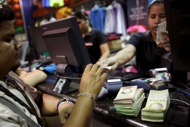 A man pays to the cashier, in Venezuelan bolivar notes, at a shopping center in Caracas, Venezuela, December 9, 2015.  REUTERS/Carlos Garcia Rawlins