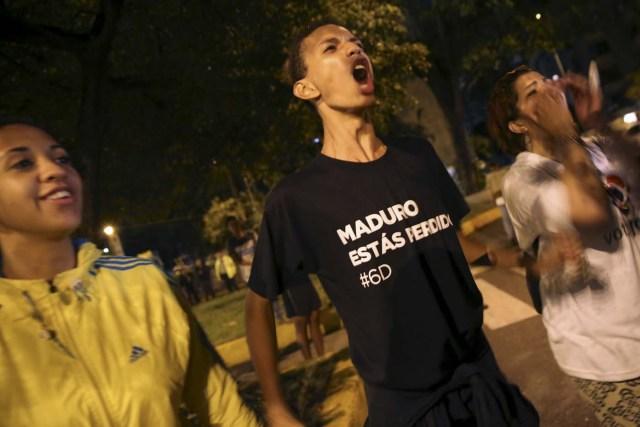 """Un seguidor de la oposición en Venezuela con una franela en la que se lee """"Maduro estás perdido"""" grita mientras celebra en Caracas la victoria en las elecciones legislativas de la coalición Mesa de la Unidad Democrática (MUD), 7 de diciembre de 2015.  Como un león herido, el chavismo venezolano se guarecerá hasta que sanen sus heridas tras la aparatosa derrota que le propinó la oposición en las elecciones parlamentarias del fin de semana, e iniciará una serie de reuniones intestinas para autoevaluarse. REUTERS/Nacho Doce"""